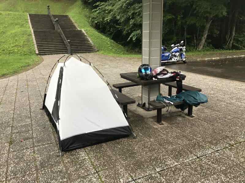 雨の中の上士幌航空公園キャンプ場の東屋とテント